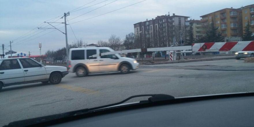Araçlar bariyeri kapalı olan tren yolundan geçiyor
