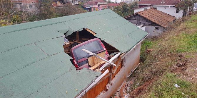 Evin çatısına uçan araç, tavanı parçalayıp salona düştü