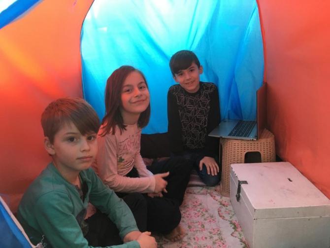 3 kardeş balkonda kurdukları çadırda ders çalışıyor