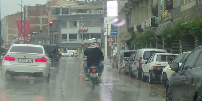 Bursa'da motosiklet sürücüsünden sağanak yağmura karşı kovalı önlem!